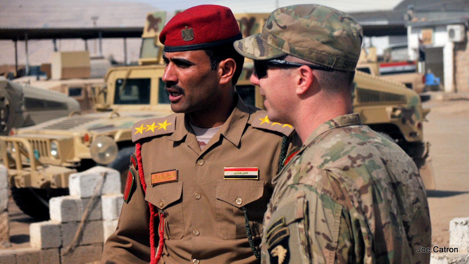 In this Sept. 6, 2016 photo released by the U.S. Army, U.S. Army Capt. Gerrard Spinney, right, commander of Company C, 1st Squadron, 75th Cavalry Regiment, Task Force Strike, speaks to his Iraqi army counterpart from the Ninawa Operations Command prior to a security meeting at Camp Swift, Iraq.