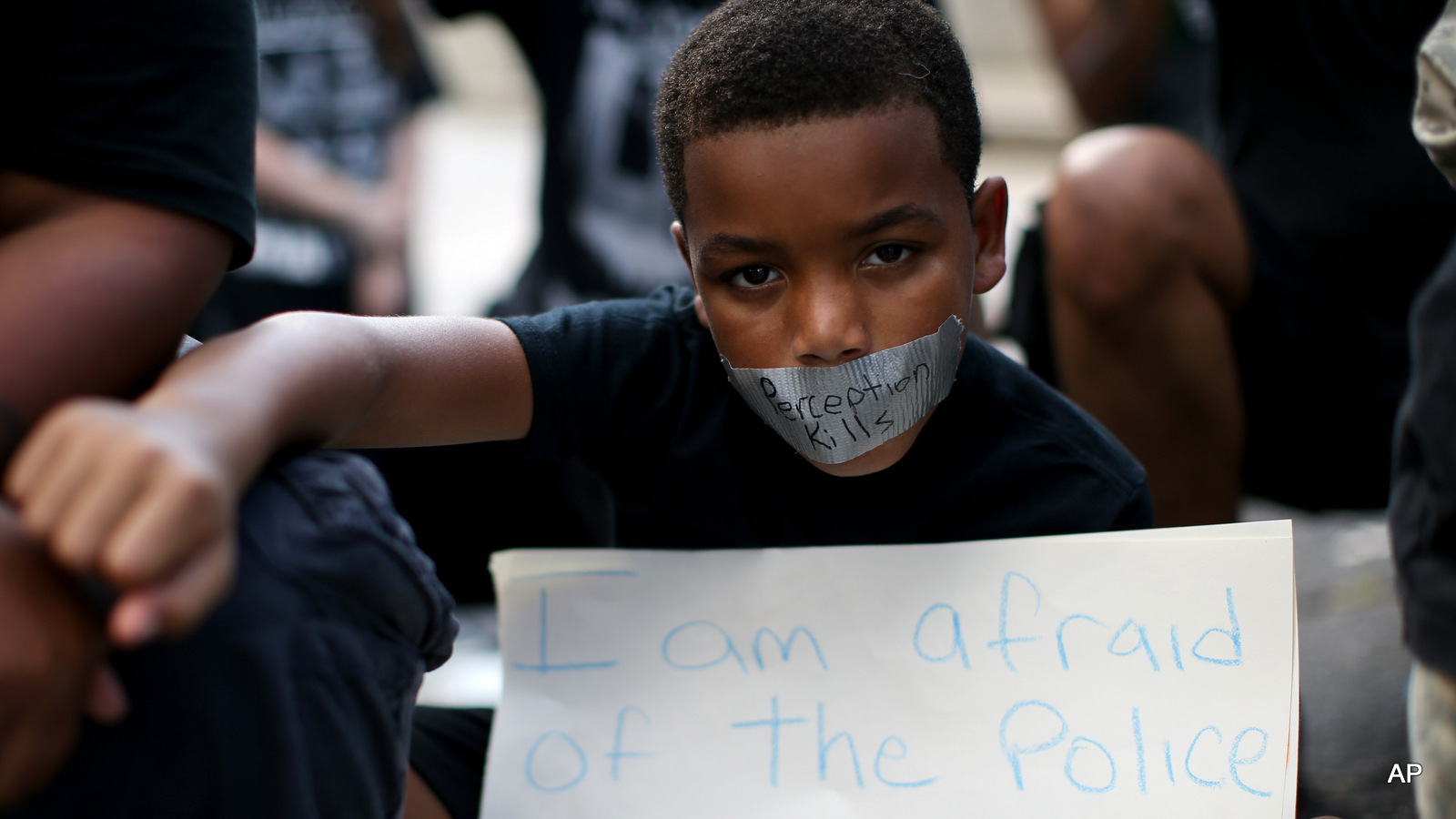 A young boy holds his fist up while wearing tape over his mouth during a Black Lives Matter protest at an entrance to Lenox Square Mall in Atlanta, Saturday, Sept. 24, 2016, in response to the police shooting deaths of Terence Crutcher in Tulsa, Okla. and Keith Lamont Scott in Charlotte, N.C. The Black Lives Matter chapter of Atlanta is boycotting major retailers following the recent police shooting deaths involving black men.