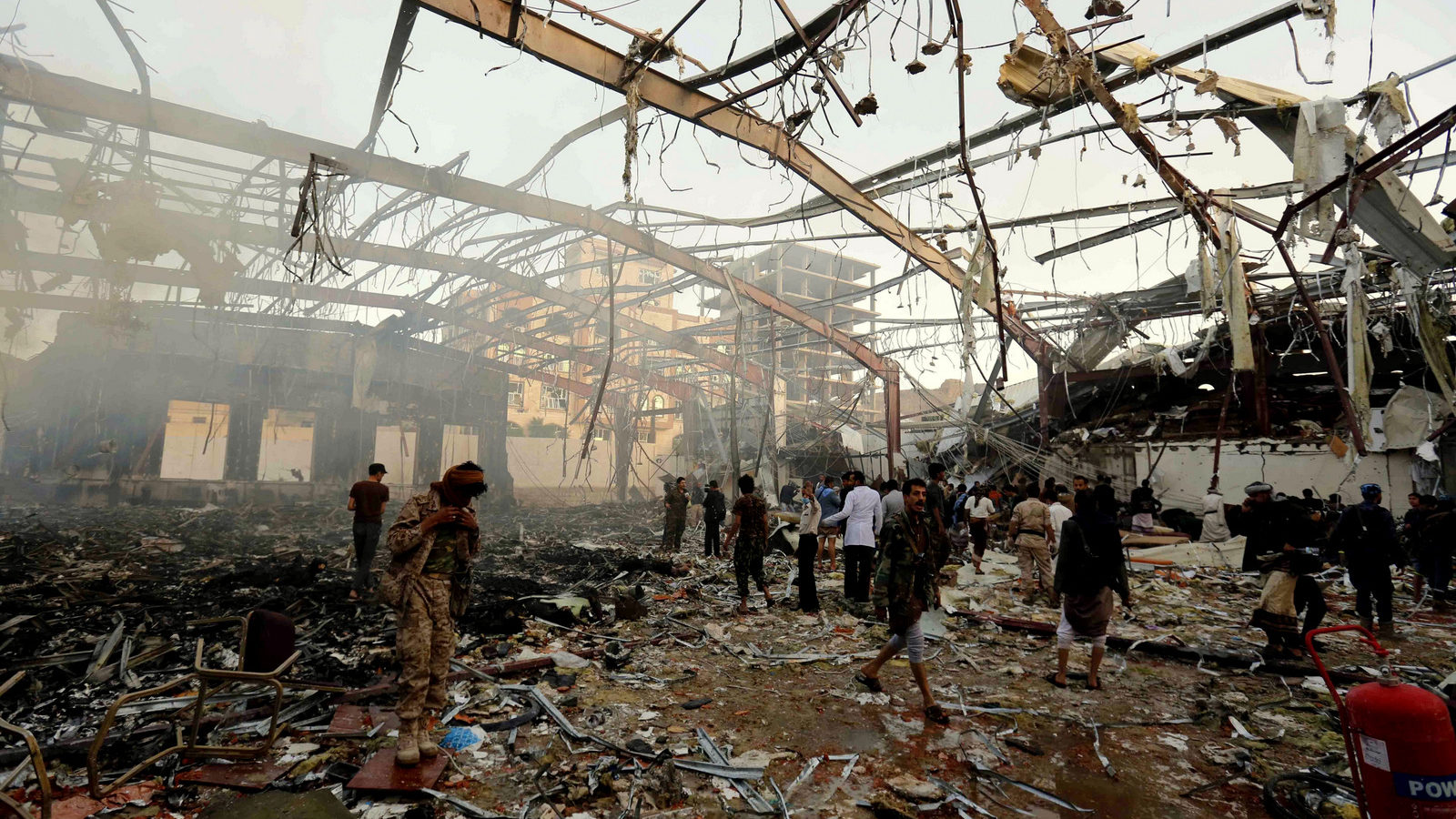 People inspect the aftermath of a Saudi-led coalition airstrike on a funeral hall in Sanaa, Yemen, Saturday, Oct. 8, 2016.