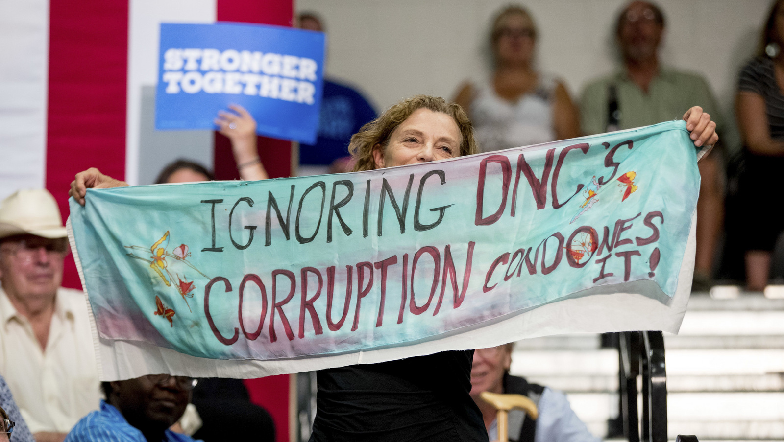 "A woman in the audience hold up fabric that reads ""Ignoring DNC's Corruption Condones It!"" as Democratic presidential candidate Hillary Clinton speaks at a rally at Adams City High School in Commerce City, Colo., Wednesday, Aug. 3, 2016. (AP Photo/Andrew Harnik)"