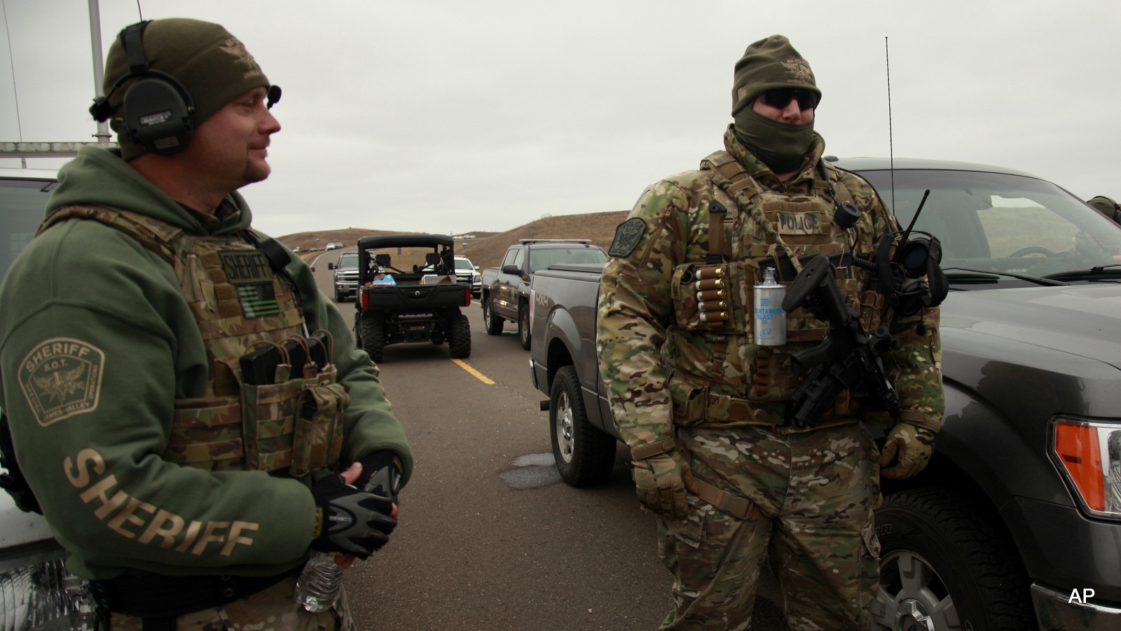 Two members of the Stutsman County SWAT team talk while deployed to watch protesters demonstrating against the Dakota Access Pipeline encroaching the water source near the Stand Rock Sioux Reservation, as they stand next to a police barricade on Highway 1806 in Cannon Ball, N.D., Sunday, Oct. 30, 2016.