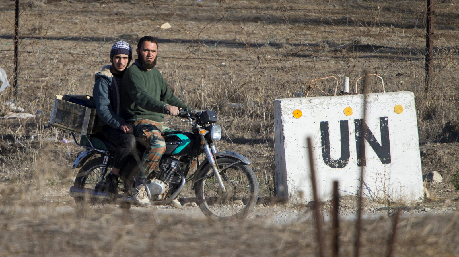Two men, not specified which group of rebels, ride a motorcycle towards an abandoned UN base at Syria's Quneitra border crossing between Syria and the Israeli-controlled Golan Heights, Monday, Nov. 28, 2016. (AP Photo/Ariel Schalit)