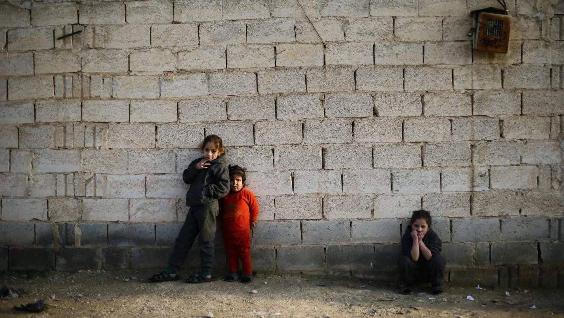In this Wednesday, Jan. 18, 2017 photo, Syrian girls who fled from the village of Deir Hafer with their family watch their brothers playing in the town of Safira, just south of Aleppo, Syria, Wednesday, Jan. 18, 2017. As Islamic State-held areas in northern Syria come increasingly under attack by an assortment of groups, thousands of civilians have been risking their lives to make the perilous journey out, paying smugglers to escape the shelling and the extremist group's terror, many of them opting to go to government-controlled territory. (AP Photo/Hassan Ammar)