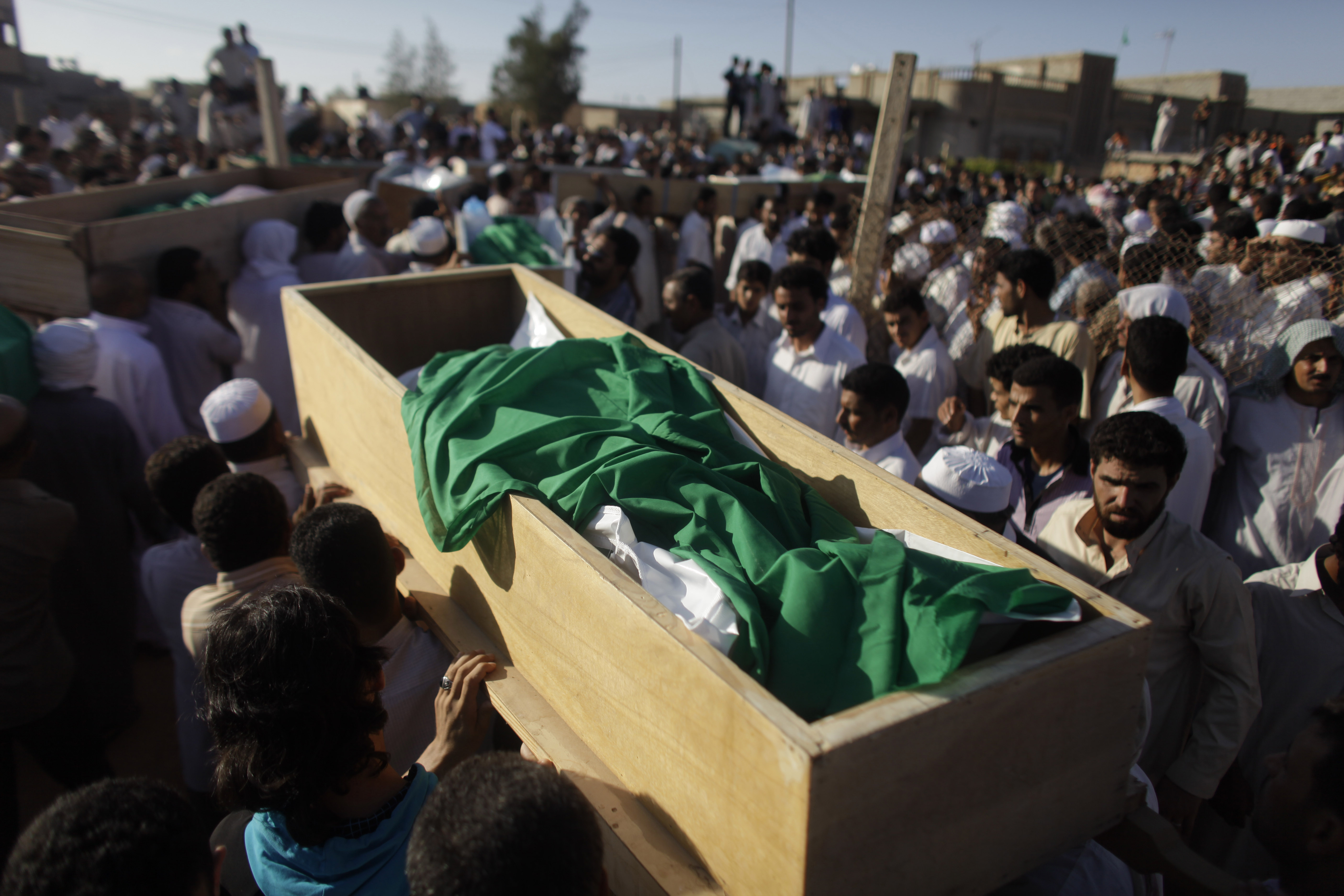 Men carry coffins during the burial of more than two dozen people after an alleged NATO bombing in the town of Majar, near in Zlitan, Libya, Aug. 9, 2011. Several homes were hit and reportedly 28 people, some of them women and children, were later buried. (AP/Dario Lopez-Mills)