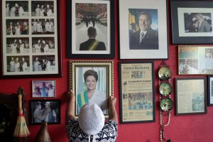 "Maria de Jesus Oliveira da Costa, known as ""Tia Zelia,"" takes down an autographed photo given to her by Brazil's impeached President Dilma Rousseff, to show it to journalists at her restaurant in Brasilia, Brazil, where photos of former President Luiz Inacio Lula da Silva also hang. (AP/Eraldo Peres)"