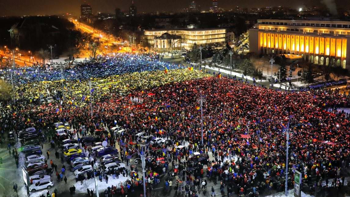 People light the flashes of their mobile phones in the colors of Romania's flag during an anti-government protest in Bucharest, Romania, Sunday, Feb. 12, 2017. Protesters braved freezing temperatures gathering outside the government headquarters for the 13th consecutive day to demand the government's resignation after it passed a decree that would have diluted the anti-corruption fight that has targeted top officials.(AP/Vadim Ghirda)