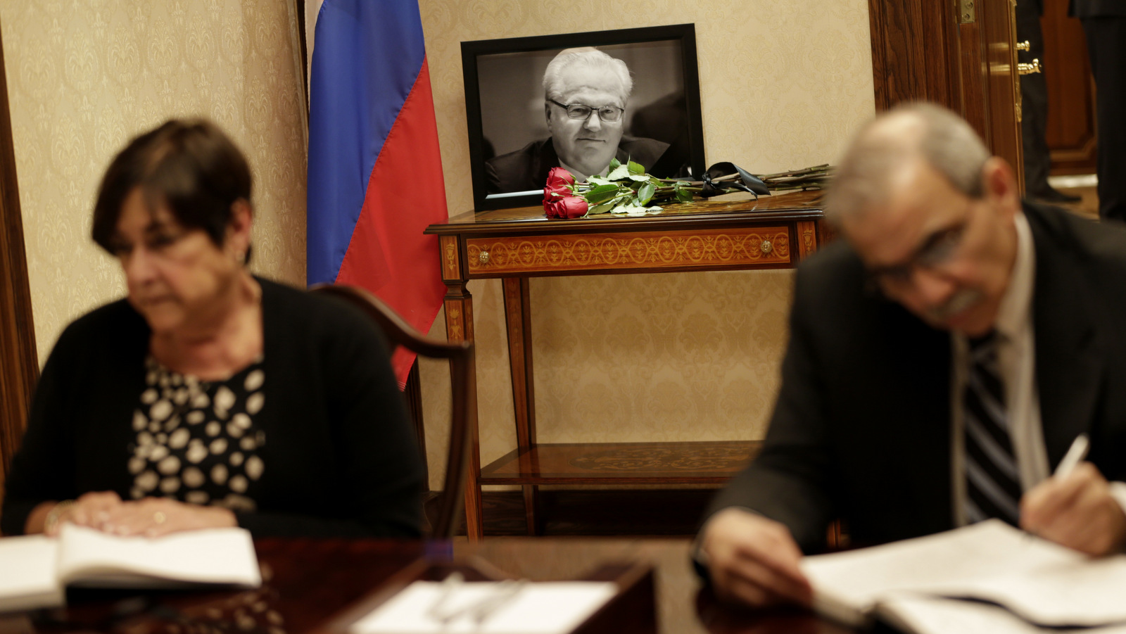 A picture of Vitaly Churkin, Russia's ambassador to the United Nations, is displayed while people sign condolences books at the Russian Mission to the U.N. in New York, Tuesday, Feb. 21, 2017. The city medical examiner was expected to perform an autopsy Tuesday on Russia's ambassador to the U.N., who died a day earlier after falling ill at his office at Russia's U.N. mission. (AP/Seth Wenig)
