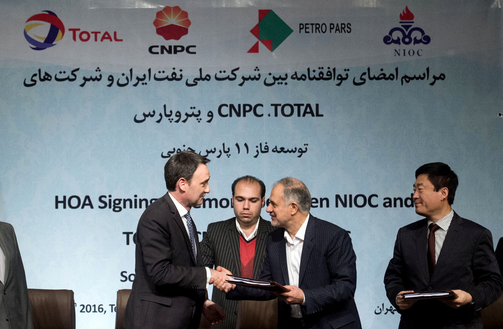Head of the Middle East and North Africa division at Total, Stephane Michel, left, and managing director of the National Iranian Oil Company Ali Kardor, right, shake hands after signing a $4.8 billion gas agreement in Tehran, Iran, Tuesday, Nov. 8, 2016. (AP/Ebrahim Noroozi)