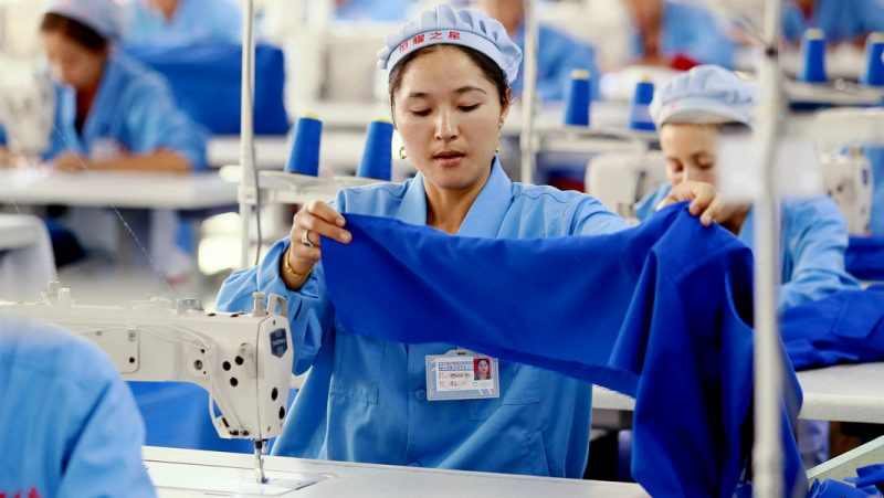 Chinese workers sew clothes at a garment factory in Wuqia town, Kuqa county, Aksu Prefecture, northwest China' class=