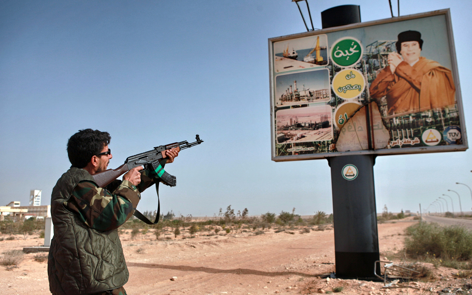 An armed Libyan rebel shoots an AK-47 at a poster of Muhammar Gaddafi in the captured rebel town of Ras-Lanuf in the east of the country (Photo: Andrey Stenin/Sputnik)