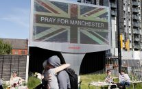 A couple embrace under a billboard in Manchester city centre, Tuesday May 23, 2017, the day after the suicide attack at an Ariana Grande concert that left 22 people dead as it ended on Monday night. (AP/Kirsty Wigglesworth)