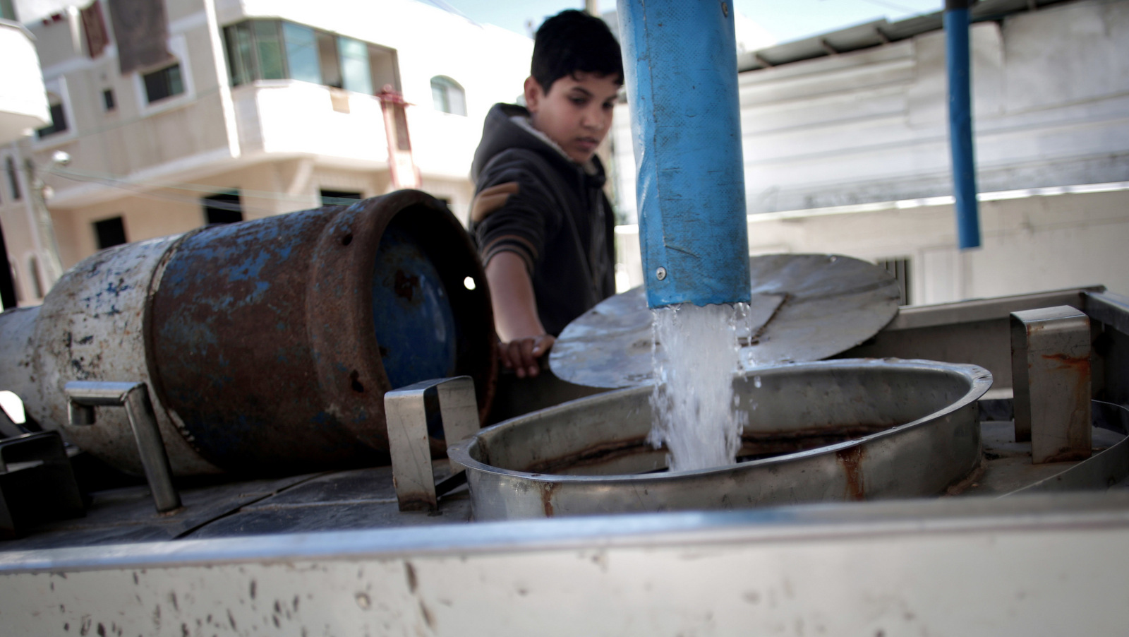 A Palestinian man fills tankers with drinking water for sale at a drinking water station in Gaza City. Poor sewage treatment is a feature of life in Gaza, a result of infrastructure damaged during wars with Israel and a chronic shortage of electricity to run wastewater plants. (AP/Khalil Hamra)