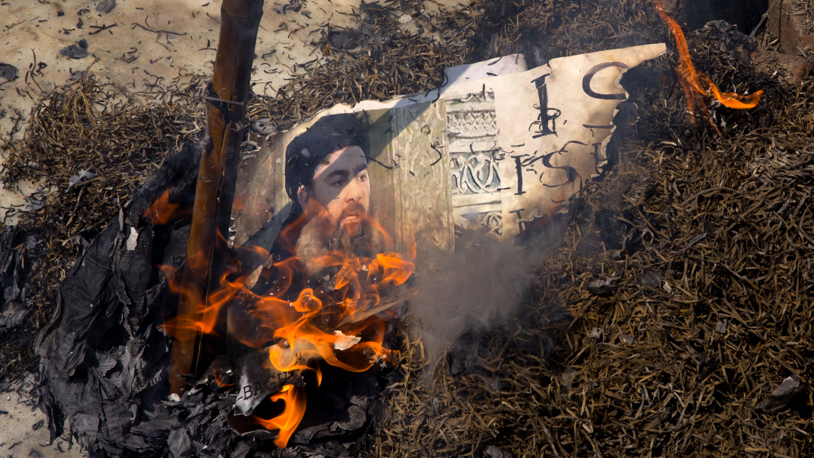 Shia Muslims burn an effigy of the leader of the ISIS, Abu Bakr al-Baghdadi during a protest in New Delhi, India, Friday, June 9, 2017. The protest was sparked by the Wednesday's attacks on Iran's parliament and the tomb of its revolutionary leader that killed over a dozen. The banner read: ISIS equals Satan. (AP/Manish Swarup)