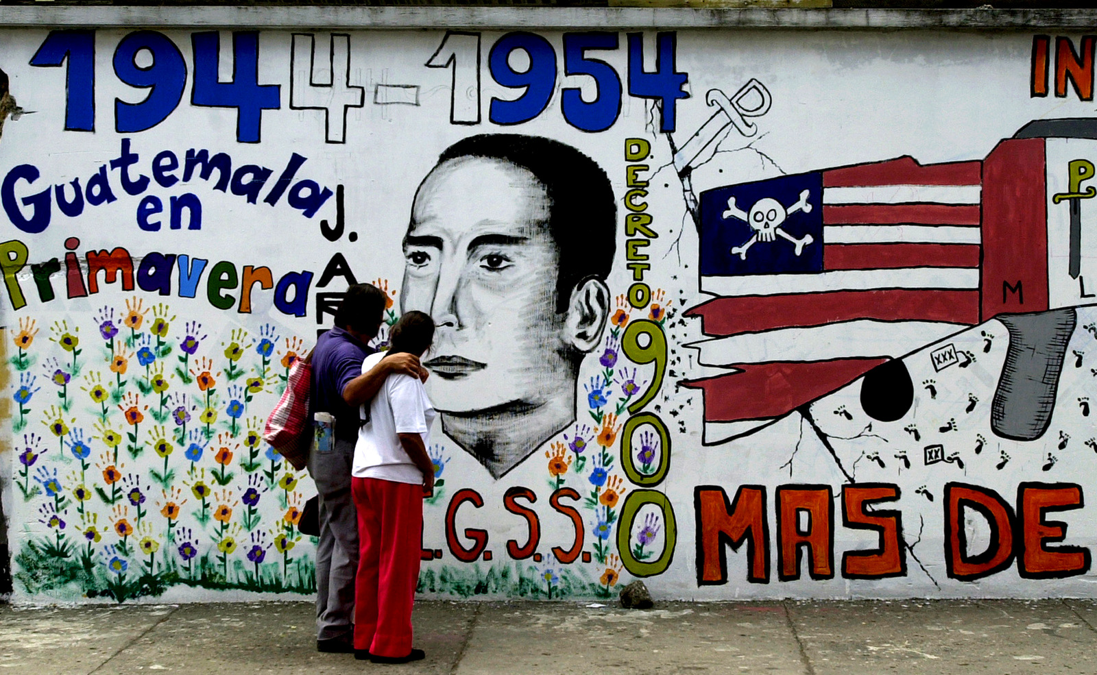 A couple walks by a mural in downtown Guatemala City commemorating the 50th anniversary of a CIA backed military intervention that ousted leftist president Jacobo Arbenz in Guatemala. (AP/Rodrigo Abd)