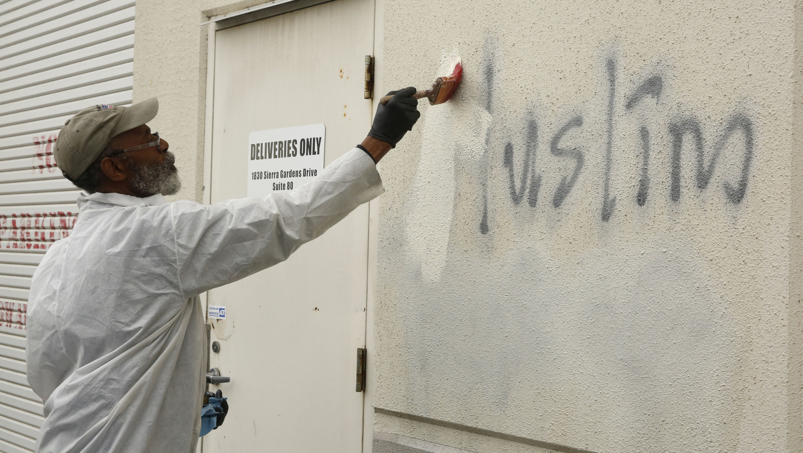Willie Lawson paints over racist graffiti painted on the side of a mosque in Roseville, Calif. (AP/Rich Pedroncelli)