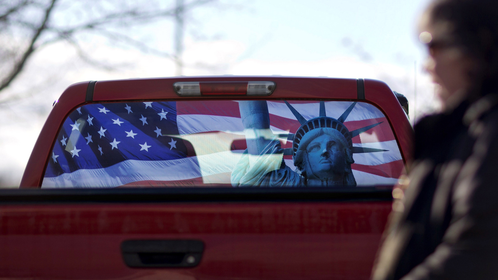A pickup truck with a rear window decorated in the theme of the American flag and Statue of Liberty, sits in the parking lot in Manchester, N.H. (AP/David Goldman)
