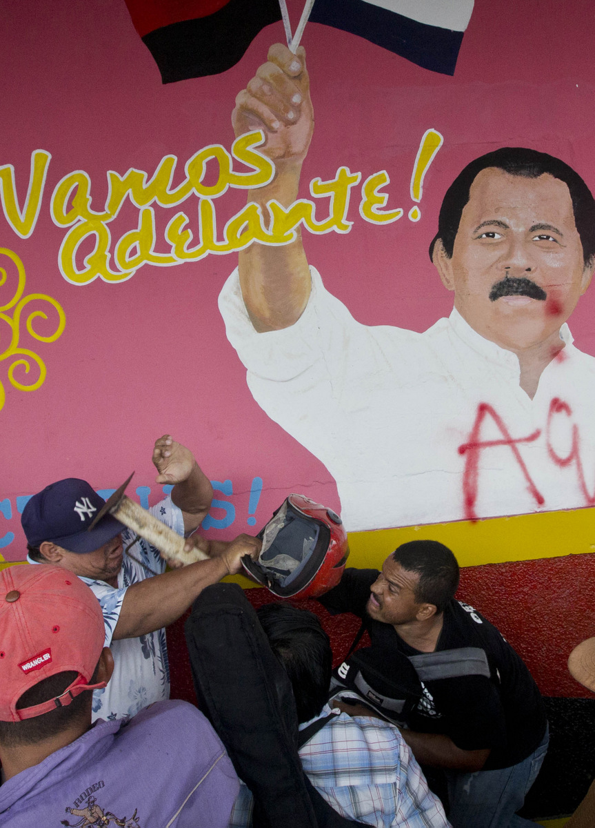 "A farmer opposed to the transoceanic canal project hits a government supporter over the head with a galvanized pipe mortar, backdropped by a wall that depicts a likeness of President Daniel Ortega with the message, ""Let's move forward!"" in Juigalpa, Nicaragua, June 13, 2015. (AP/Esteban Felix)"
