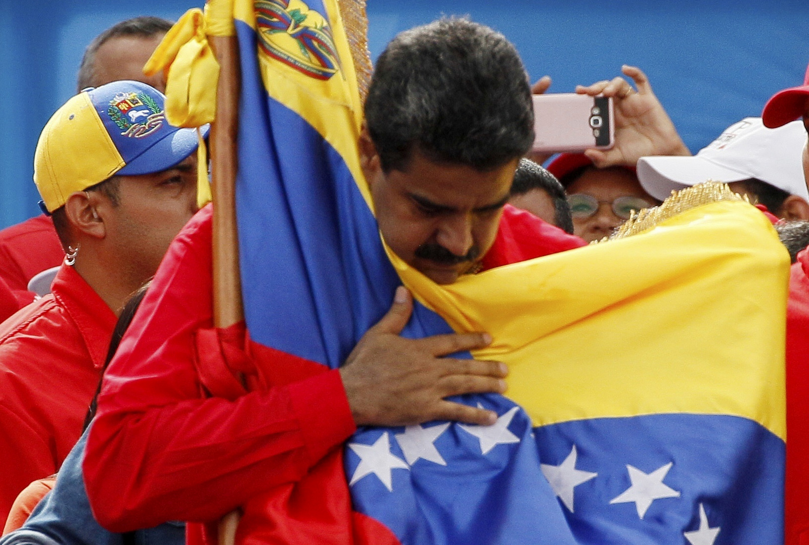 Venezuela's President Nicolas Maduro holds the country's national flag during a rally in Caracas, Venezuela, July 27, 2017. (AP/Ariana Cubillos)