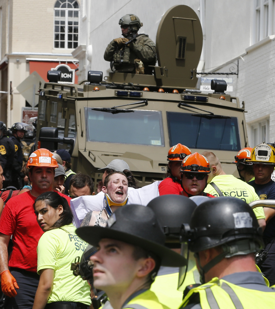Rescue personnel help injured people while police patrol in armored vehicles after a car ran into a large group of protesters after an white nationalist rally in Charlottesville, Va., Aug. 12, 2017. (AP/Steve Helber)