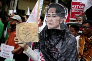 A woman wears a mask of Myanmar's Foreign Minister Aung San Suu Kyi during a rally against the persecution of Rohingya Muslims, outside the Embassy of Myanmar in Jakarta, Indonesia, Nov. 25, 2016. (AP/Dita Alangkara)