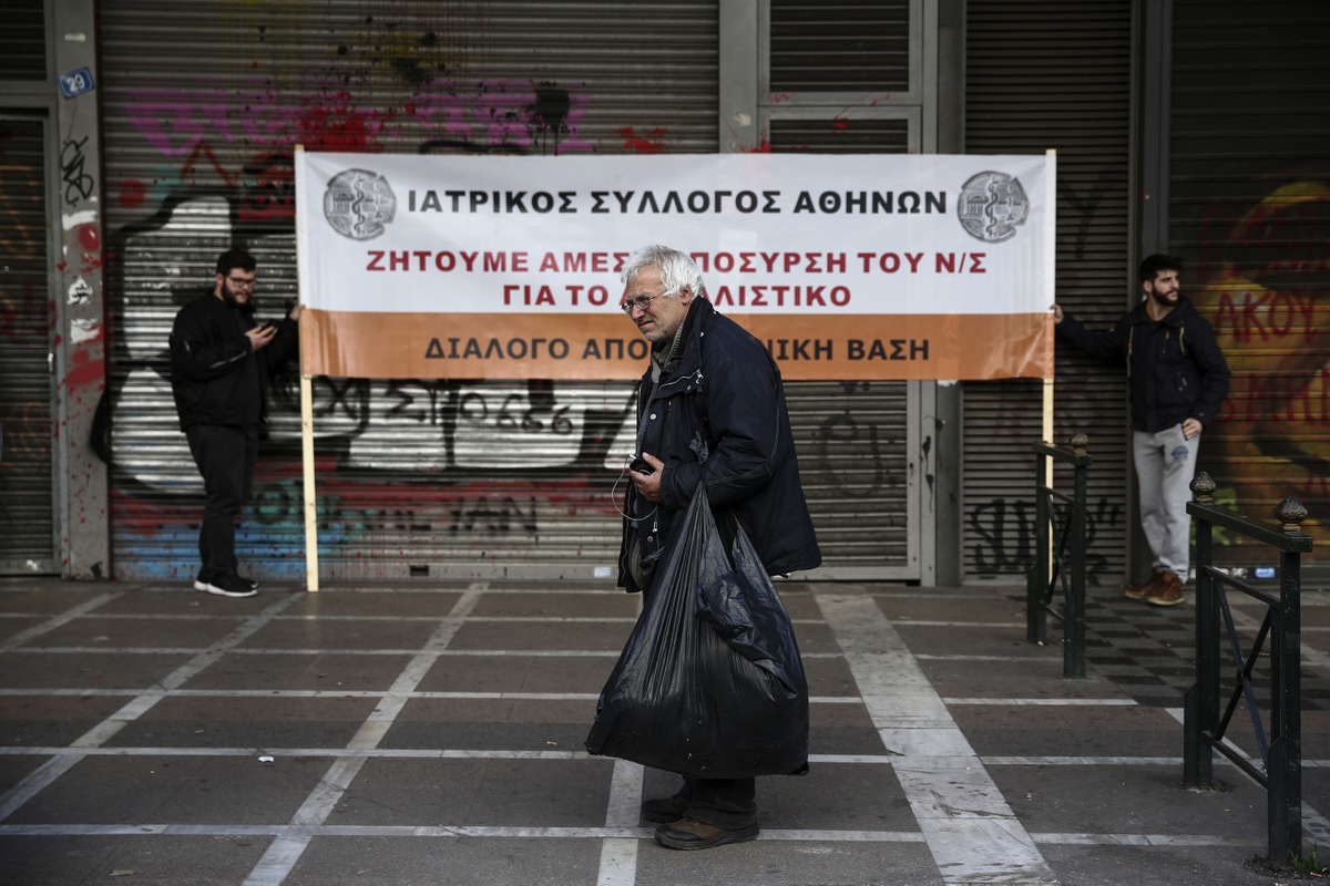 "A man stands in front of a banner during an anti-austerity rally by workers in the health sector outside the Labour ministry in Athens, March 2, 2017. Monitors from Greece's European Union creditors and the International Monetary Fund re-launched talks in Athens on Tuesday on the country's stumbling bailout program. The banner reads : ""Medical Association of Athens, We demand the immediate withdraw of the pension bill"". (AP/Yorgos Karahalis)"