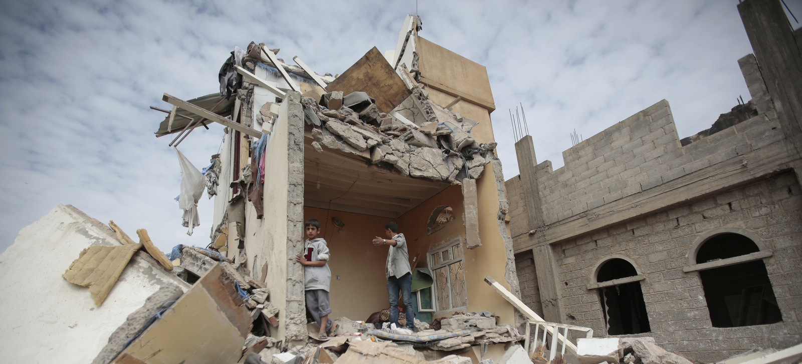 Boys stand on the rubble of a house destroyed by Saudi-led airstrikes in Sanaa, Yemen, Friday, Aug. 25, 2017. Airstrikes by a Saudi-led coalition targeted Yemen's capital early on Friday, hitting at least three houses in Sanaa and killing at least 14 civilians, including women and children, residents and eyewitnesses said. (AP Photo/Hani Mohammed)