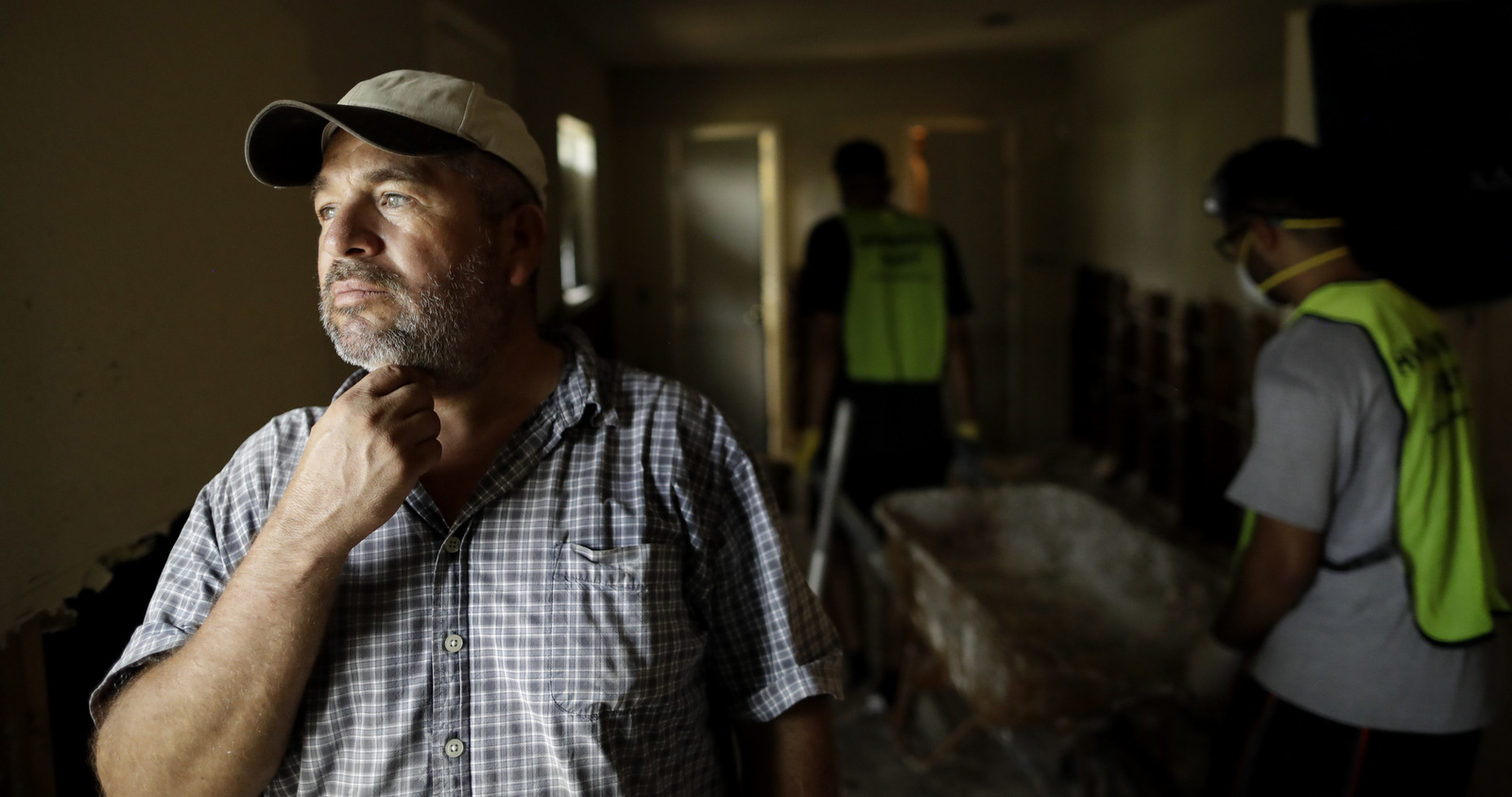 In this Sunday, Sept. 3, 2017, photo, Lino Saldana looks out his window towards the bayou that overflowed into his home as volunteers from the Ahmadiyya Muslim Youth Association help him clean out debris in Houston. Like many of his neighbors on flood-ravaged Minden Street, Saldana knows that if he doesn't work, he doesn't get paid. Harvey's epic 52 inches of rain didn't discriminate between rich and poor areas with its flooding, but in working-class neighborhoods where many live paycheck to paycheck, the cleanup and recovery could be an even tougher slog. (AP/Gregory Bull)