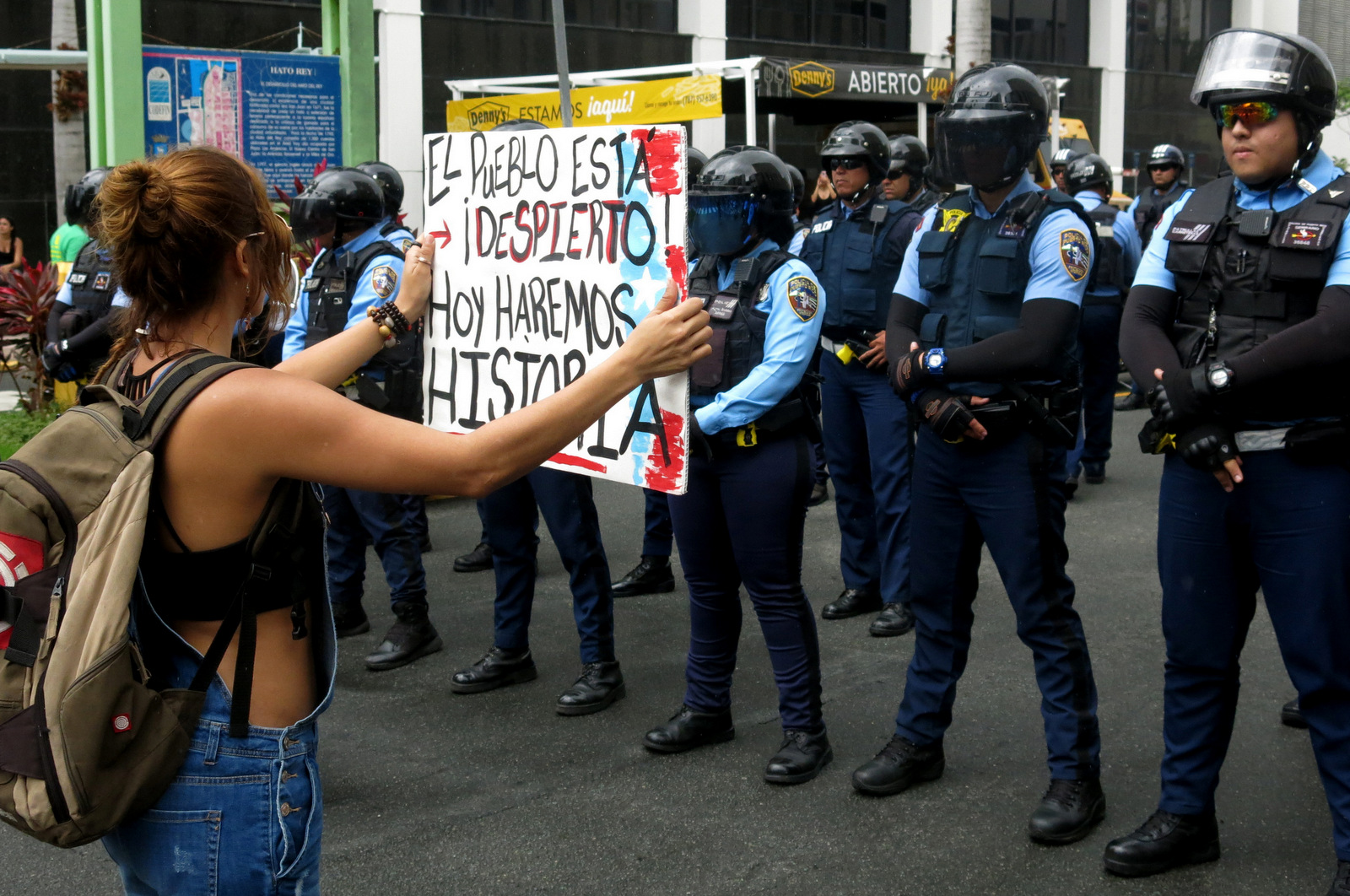 "A woman holds a sign up to police that reads in Spanish ""The people are awake. Today we'll make history"" during a May Day protest against looming austerity measures amid an economic crisis and demanding an audit on the island's debt to identify those responsible in San Juan, Puerto Rico, May 1, 2017. Puerto Rico is preparing to cut public employee benefits, increase tax revenue, hike water rates and privatize government operations, among other things. (AP/Danica Coto)"