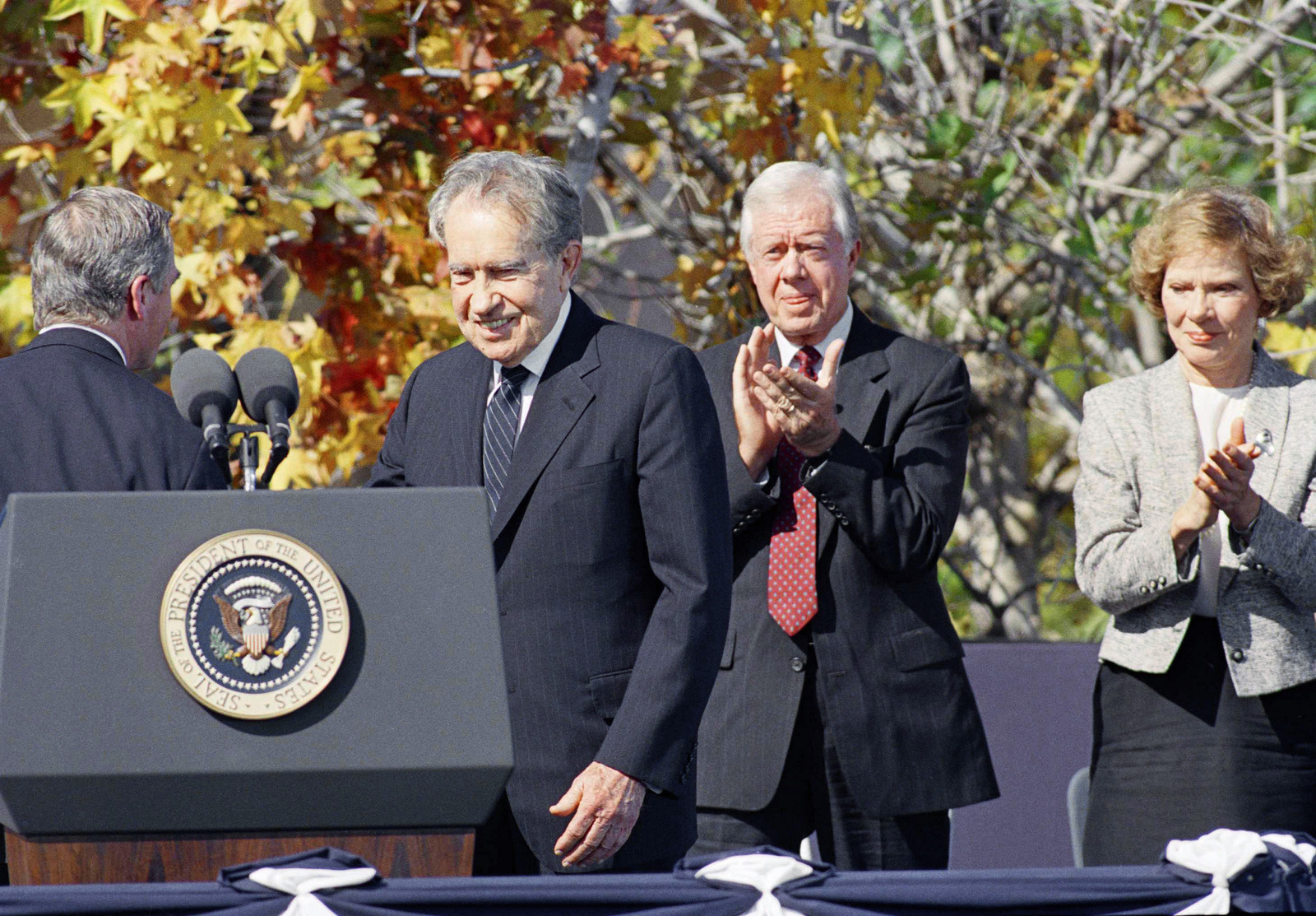Former President Jimmy Carter applauds former President Richard M. Nixon as he is introduced at the dedication ceremony for the Ronald Reagan Presidential Library in Simi Valley, California Monday, Nov. 4, 1991. The gathering was the first ever by five U.S. Presidents. (AP/Craig Fujii)
