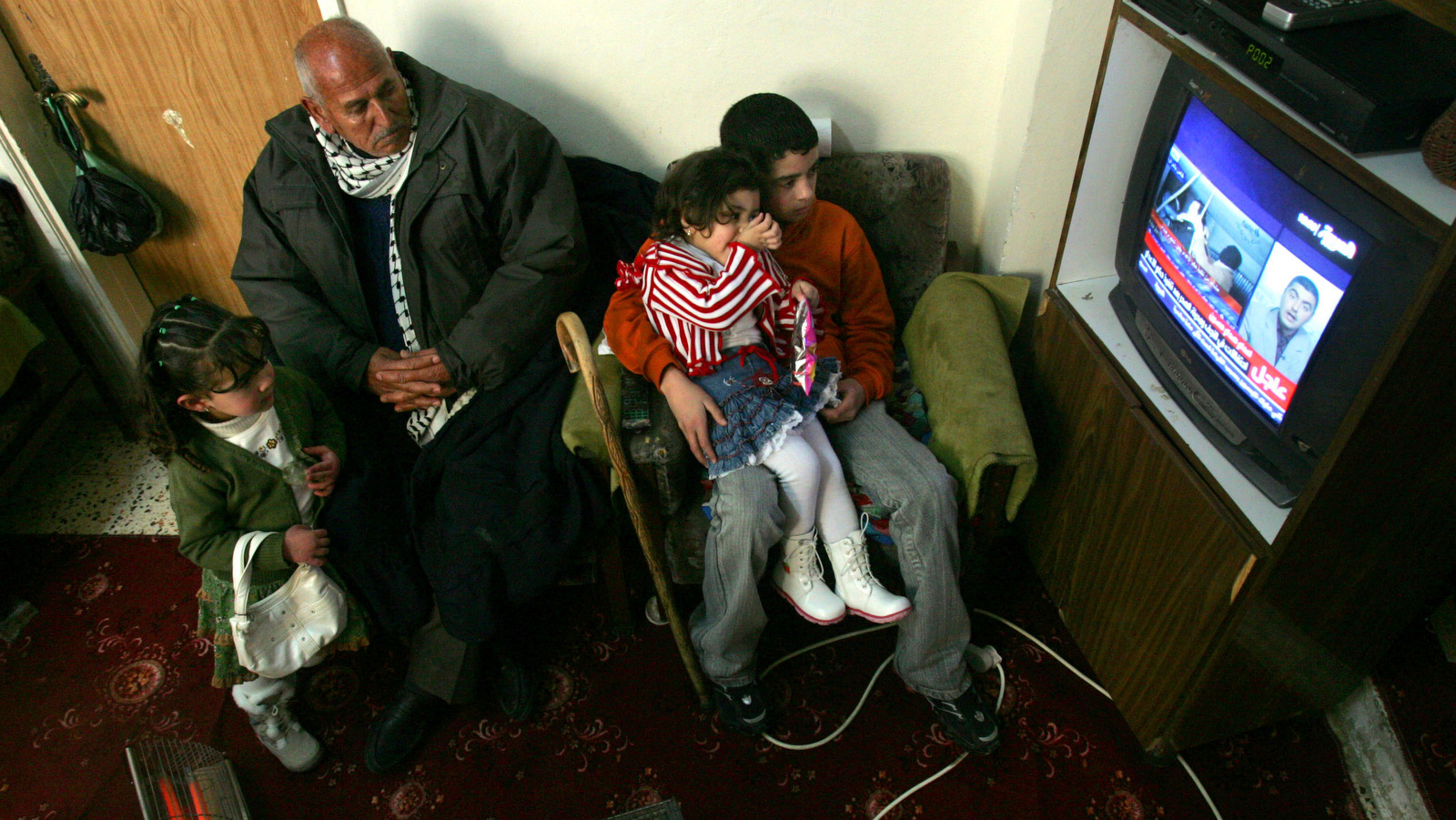 A Palestinian family watches Saudi state-owned Al-Arabiya TV transmitting a video of the execution of Saddam Hussein, in the West Bank town of Ramallah, Dec. 30, 2006. (AP/Muhammed Muheisen)