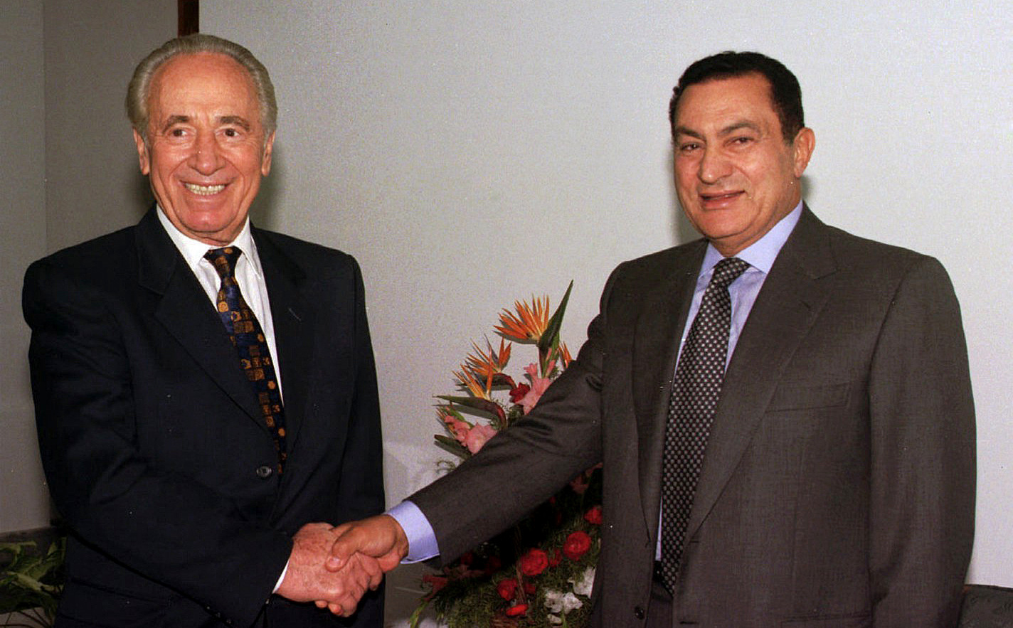 , Egyptian President Hosni Mubarak, right, shakes hands with former Israeli Prime Minister Shimon Peres at the Sharm el Sheikh resort in the Sinai peninsula for talks on the Middle East peace process, Oct. 1996. (AP/Mohamed El-Dakhakhny)