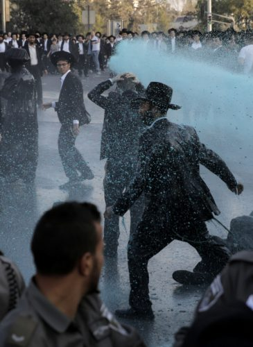 Israeli police officers spray colored water towards ultra Orthodox Jewish men during a protest against their enlistment in the army at the entrance to Jerusalem, Oct. 23, 2017. (AP/Sebastian Scheiner)