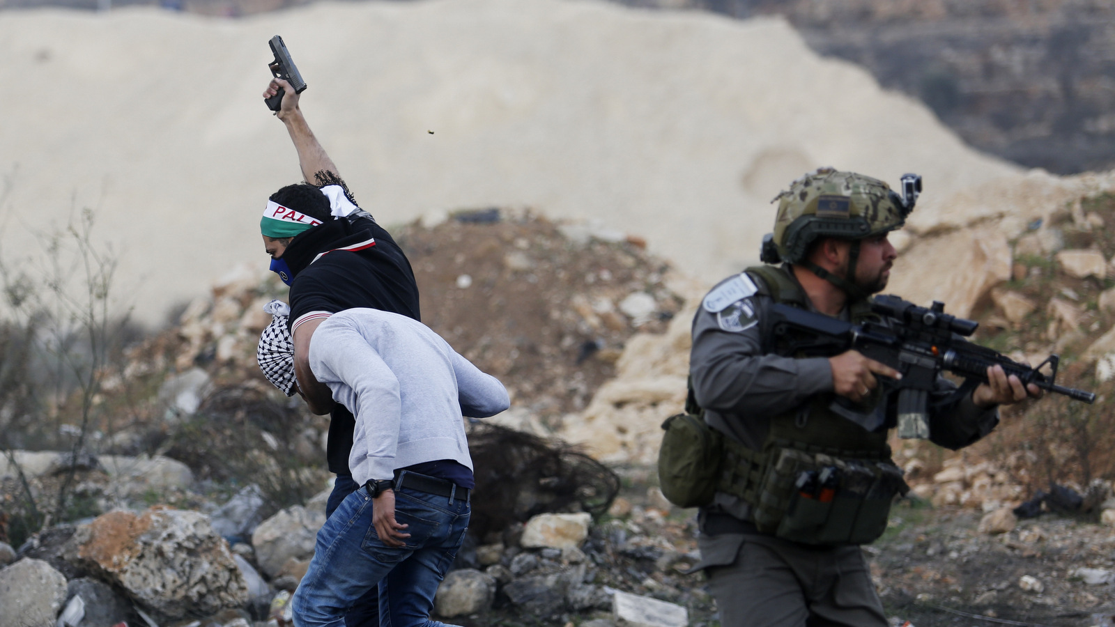 An Israeli policeman disguised as a Palestinian protester raises a pistol in air as he arrests a Palestinian demonstrator during protests against U.S. President Donald Trump's decision to recognize Jerusalem as the capital of Israel, in the West Bank city of Ramallah, Dec. 13, 2017. (AP/Nasser Shiyoukhi)
