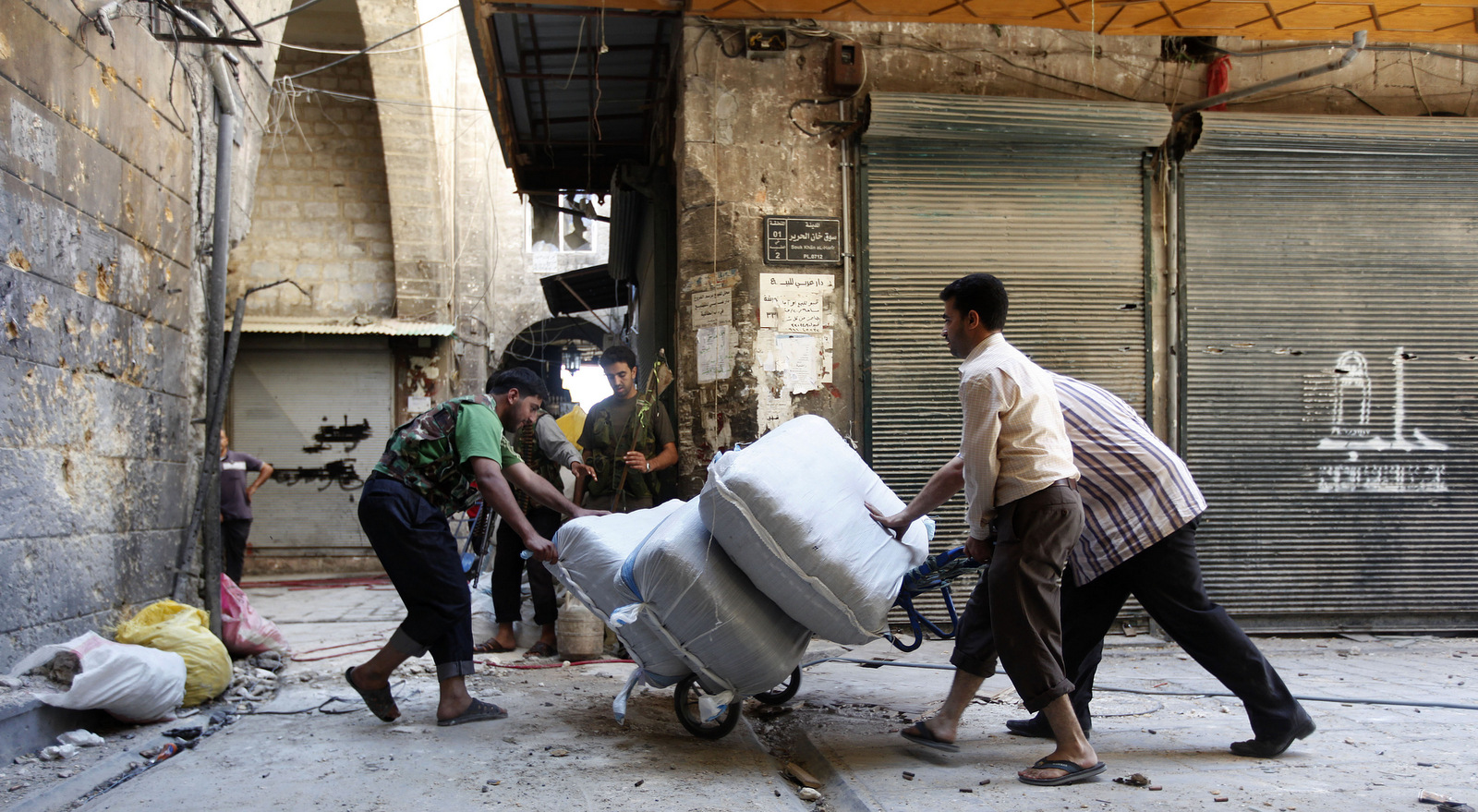 """A Free Syrian Army fighter moves supplies at the souk of the old city of Aleppo city, Syria, September 24, 2012. The Arabic on the closed shop at right reads: """"Aleppo."""" (AP/Hussein Malla)"""