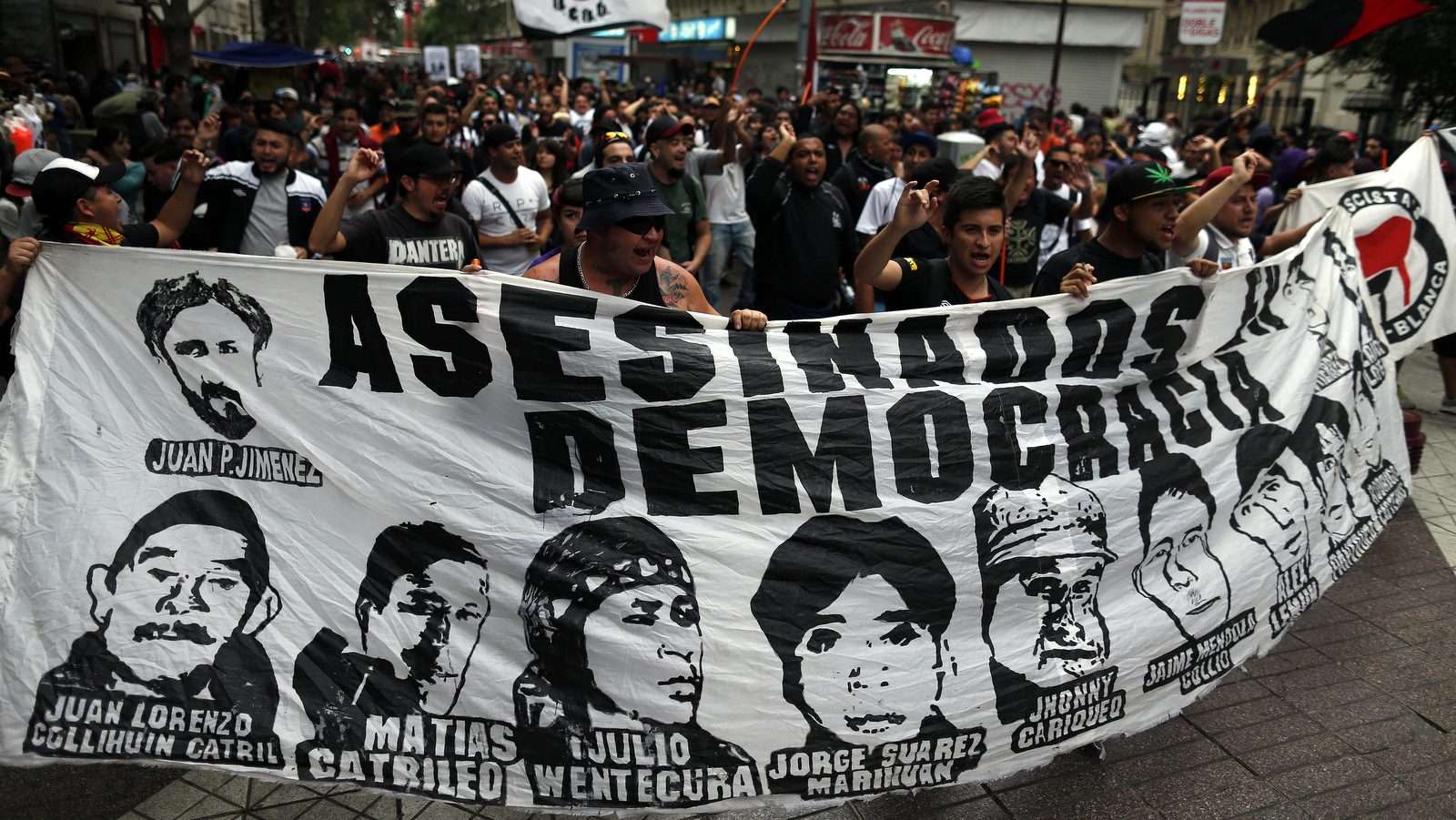 Protesters commemorate the eighth year anniversary of the police killing of Mapuche indigenous activist Matias Catrileo in Santiago, Chile, Jan. 5, 2016, carrying a banner showing the faces of protesters who have died during Chile's democratic governments. (AP/Luis Hidalgo)