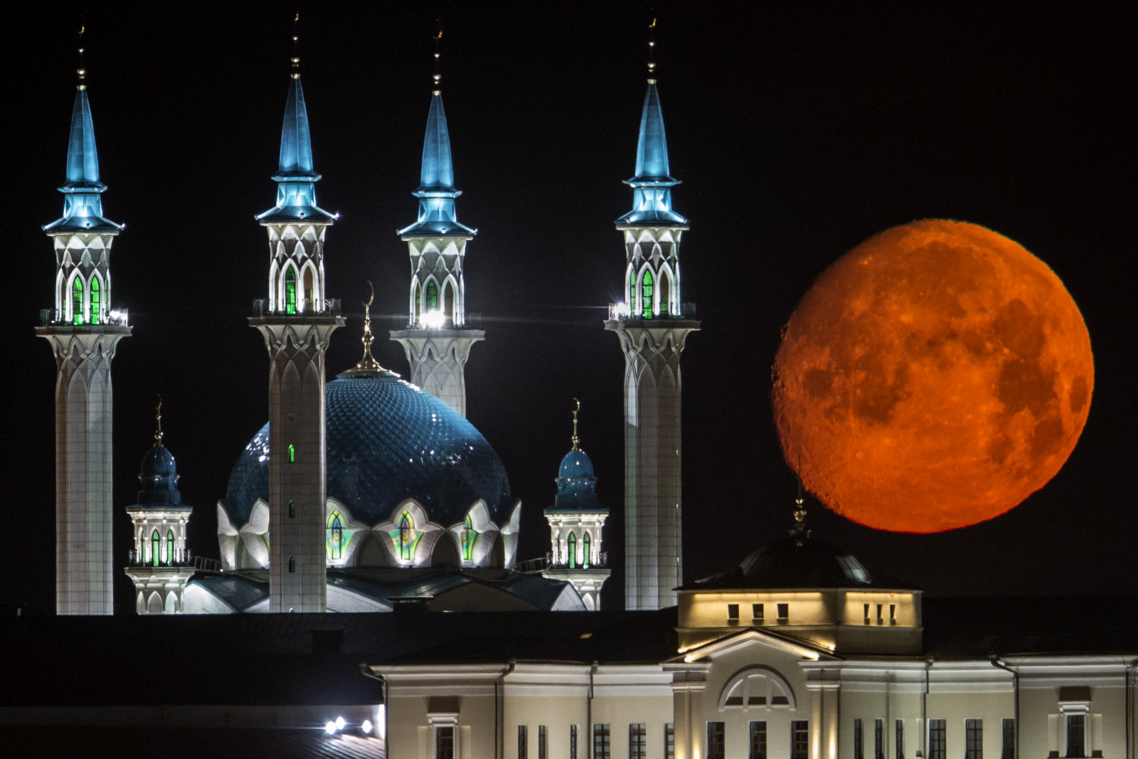 The full moon rises over the illuminated Kazan Kremlin with the Qol Sharif mosque illuminated in Kazan, the capital of Tatarstan, located in Russia's Volga River area about 700 km (450 miles) east of Moscow, July, 29, 2015. (AP Photo/Denis Tyrin)