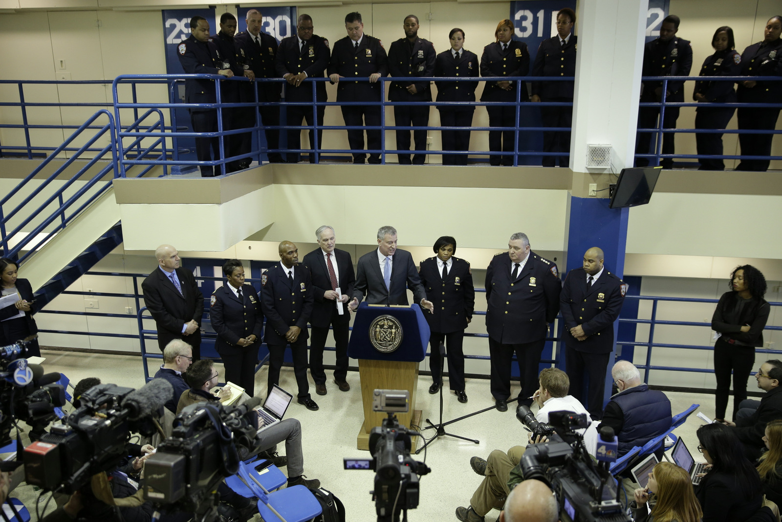 Surrounded by corrections officers, New York City Mayor Bill de Blasio holds a news conference on Rikers Island in New York, March 12, 2015. The mayor unveiled a plan to curb jail violence after a visit to the problem-plagued Rikers Island jail complex. (AP/Seth Wenig)