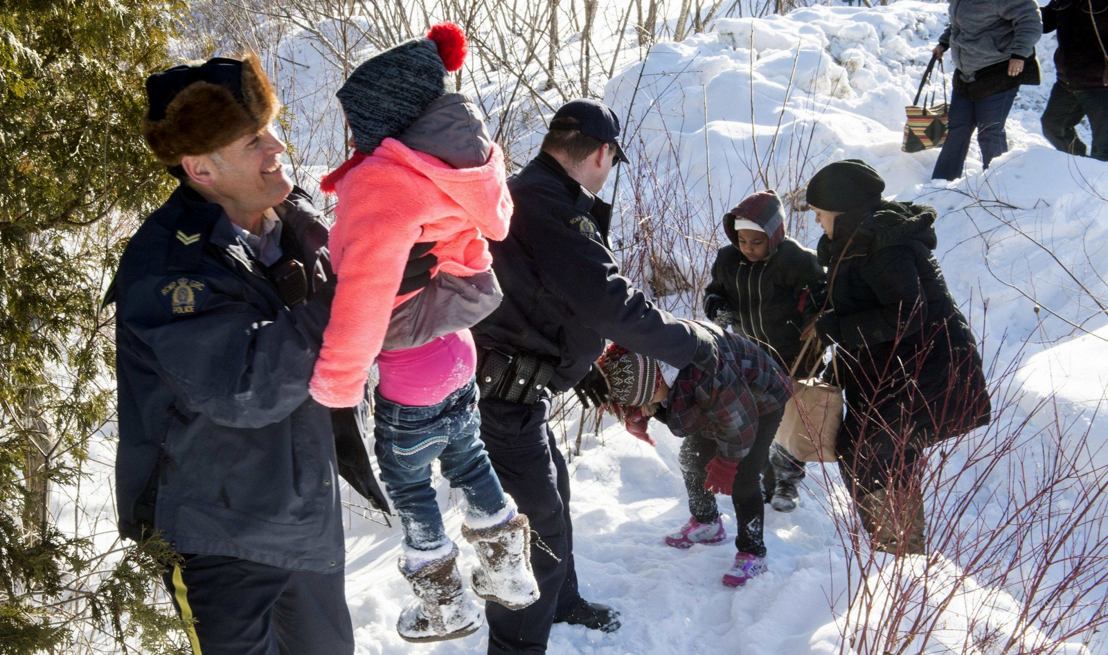 Family members are helped into Canada by Royal Canadian Mounted Police officers along the U.S.-Canada border near Hemmingford, Quebec. (Canadian Press via AP)