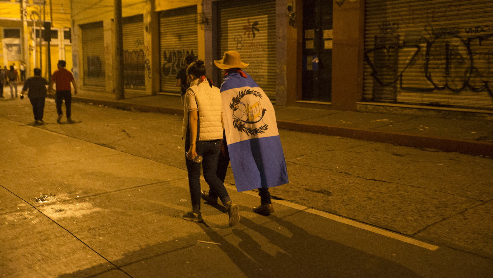 A protester with a Guatemalan flag over his shoulders walks away from Congress in Guatemala City, Jan. 16, 2017. after an extraordinary session ended, where Lawmakers repealed a recently passed bill that reduced the punishment for illegal campaign financing. Riot police dispersed the protesters with batons and pepper spray. (AP/Moises Castillo)