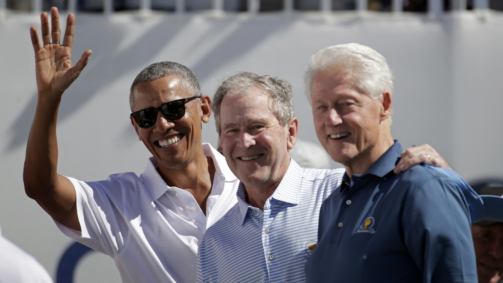 Former U.S. Presidents, from left, Barack Obama, George Bush and Bill Clinton greet spectators on the first tee before the first round of the Presidents Cup at Liberty National Golf Club in Jersey City, N.J., Sept. 28, 2017. (AP/Julio Cortez)
