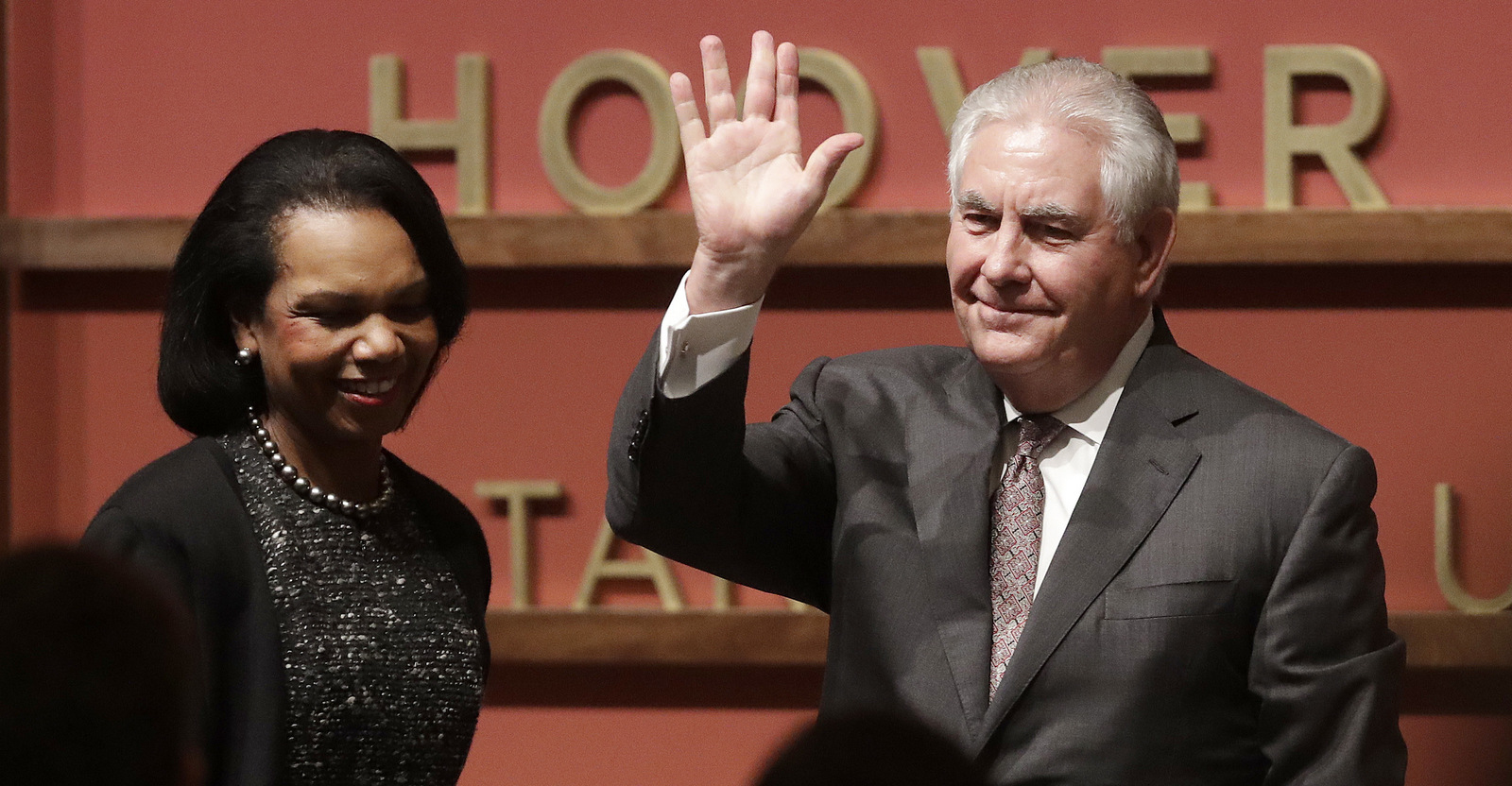 Secretary of State Rex Tillerson, right, waves after speaking to the Hoover Institution at Stanford University with former Secretary of State Condoleeza Rice, left, Jan. 17, 2018. Tillerson signaled the U.S. military will remain in Syria for the foreseeable future. (AP/Jeff Chiu)