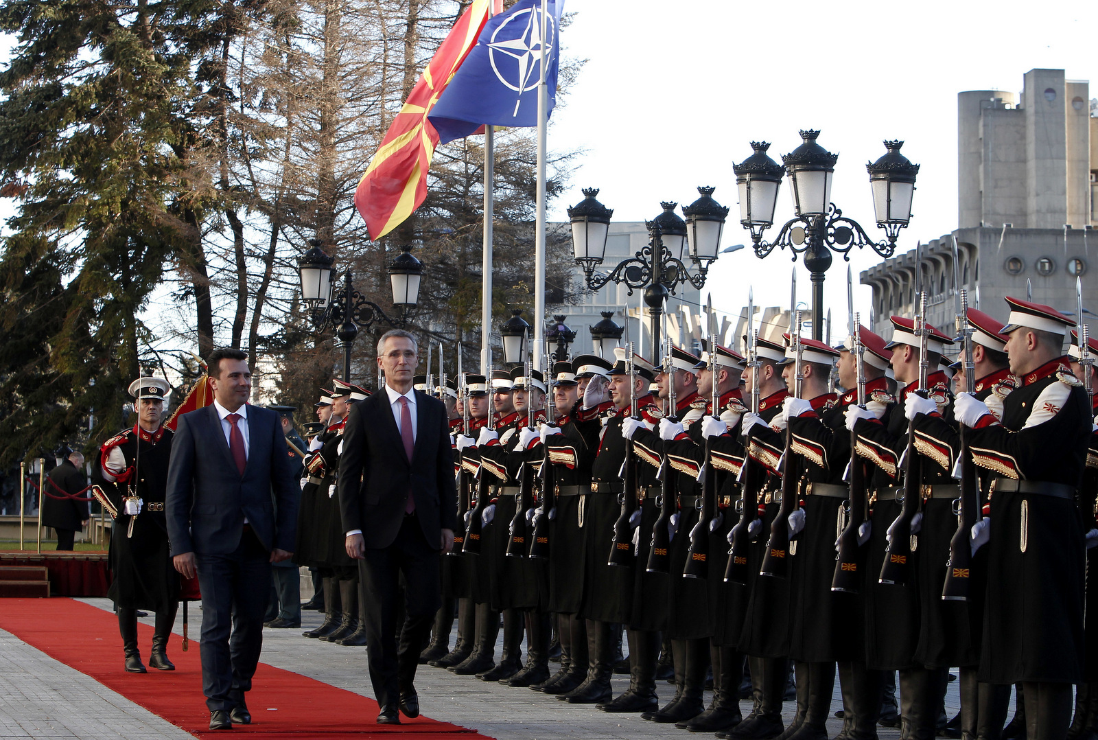 NATO Secretary General Jens Stoltenberg, second from left, accompanied by Macedonian Prime Minister Zoran Zaev, left, inspects an honor guard squad upon his arrival at the Government building in Skopje, Macedonia, Jan. 18, 2018. NATO's secretary-general urged Macedonia to solve its name dispute with Greece and proceed with wide-ranging reforms if it wants its membership bid to succeed. (AP/Boris Grdanoski)