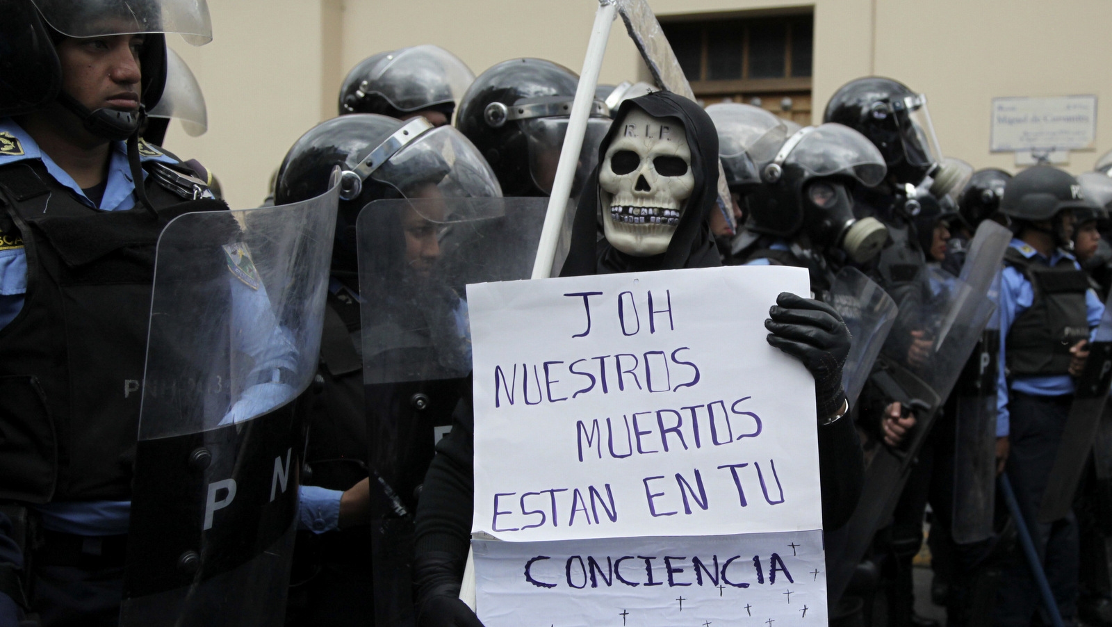 A protester wearing a grim reaper costume holds a sign with a message that reads in Spanish: