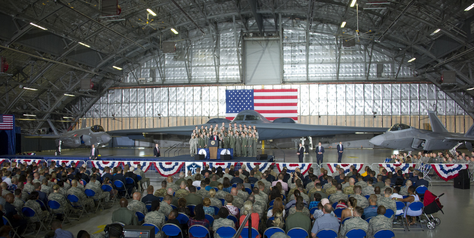 United States President Donald J. Trump delivers remarks to military personnel and families in a hanger at Joint Base Andrews in Maryland on, September 15, 2017.  He visited JBA to commemorate the 70th anniversary of the US Air Force.  In the background behind the group, from left is a F-35 Joint Strike Fighter, a B-2 Stealth Bomber and a F-22 fighter. (AP Photo)