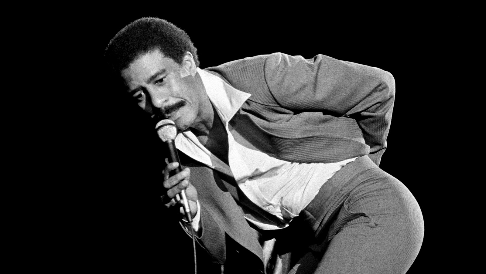 Comedian Richard Pryor gestures to the audience, after the audience jeered him for his remarks at a gathering billed as A Star Spangled Night for Rights, Sept. 19, 1977, Hollywood Bowl, Los Angeles, Calif. After the gesture, Pryor slammed the mike down and left the show. (AP/Lennox McLendon)