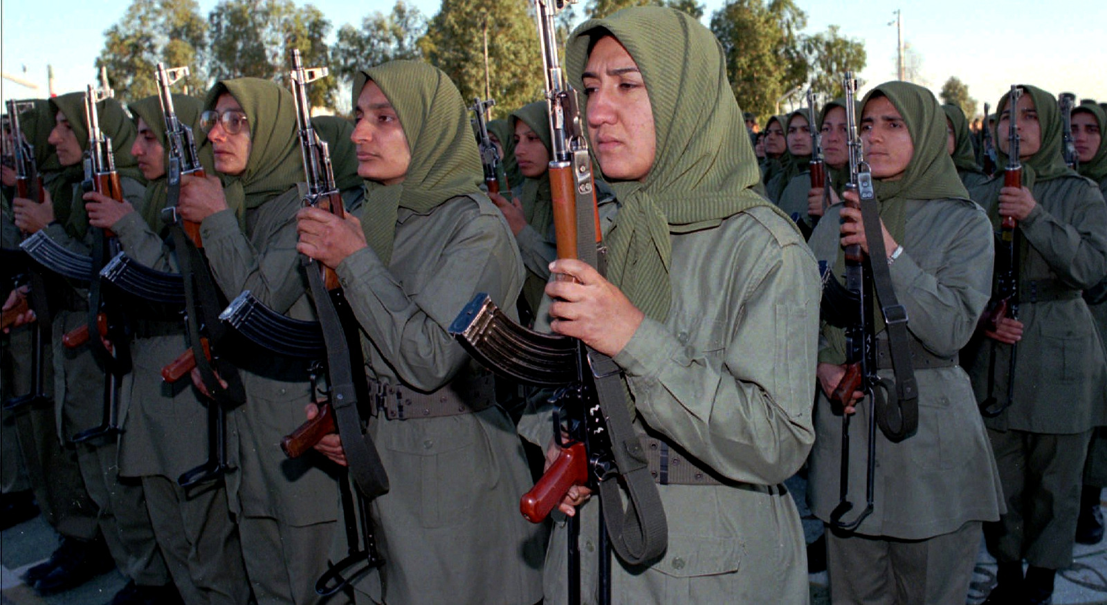 Female fighters armed with AK-47s in the National Liberation Army of Iran, a militia formed through cooperation between the MEK and Saddam Hussein, stand at attention during a flag ceremony at Camp Ashraf, Jan 29 1997, northeast of the Iraqi capital Baghdad (AP/Jassim Mohammmed)