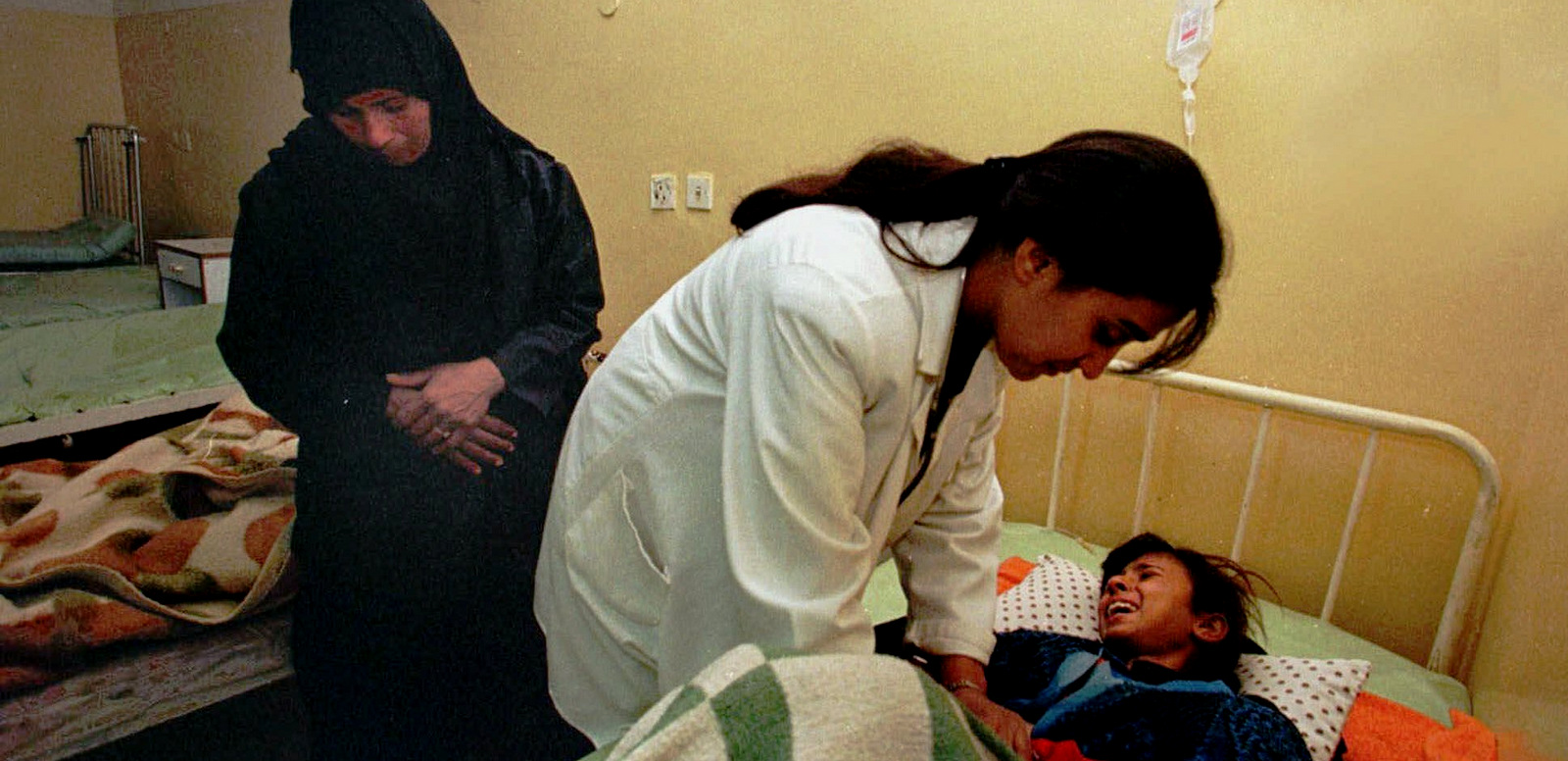 Dr. Buthayna Shibel examines a girl at the Mahawil hospital in Babylon, Iraq, Dec. 23, 1998. Economic sanctions imposed by the United States left Iraqi hospitals critically short of medicine. (AP/Murad Sezer)