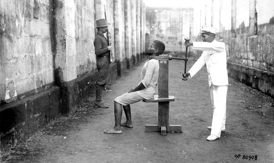 A Filipino insurrectionist is executed, one of 31 killed in Manila, Philippines on that day in 1900, with a garroting machine. An American soldier stands guard in the background. (Photo: National Archives of the Philippines)