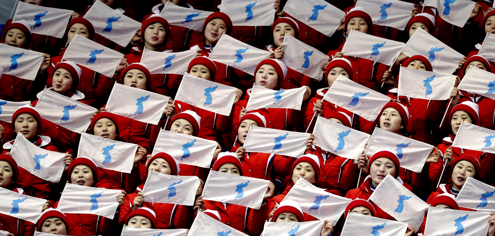 North Korea supporters wave the Korean unification flag ahead of the pairs free skate figure skating final in the Gangneung Ice Arena at the 2018 Winter Olympics in Gangneung, South Korea, Feb. 15, 2018. (AP/Bernat Armangue)