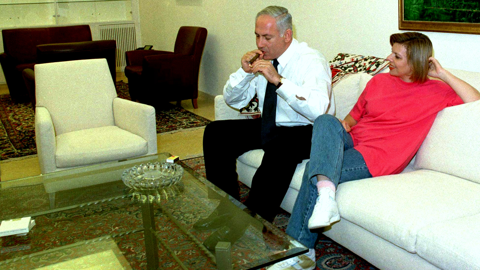 Sarah Netanyahu watches her husband, Israeli Prime Minister Benjamin Netanyahu, light a cigar in the living room of their newly refurbished official residence in Jerusalem Sunday Sept 28 1997. (AP/Zoom 77)